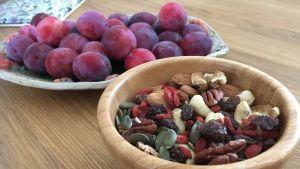 En skål med nötter, frön och russin och en skål med plommon på ett bord.