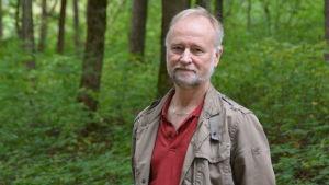 En man står i en parkskog där det finns lövträd.