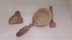 Närbild på tre stycken skedar av horn och ben i en vitrin.