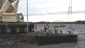 Lyftkran drar upp båt ur vattnet vid Alholmen i Jakobstad.