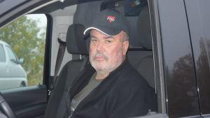 En man med svart keps och jacka sitter bakom ratten på en svart bil.