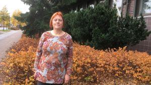 Medelålders rödhårig kvinna i brunrödgrå blus ler framför buskar och tegelbyggnad