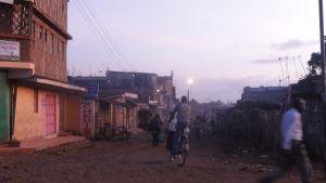 Stadsmiljö, i mitten av bilden cyklar en man.