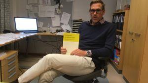 lång man i mörkblå tröja och rutig skjorta och ljusa byxor och glasögon sitter i sitt arbetsrum på en kontorsstol och håller en bok i sin hand