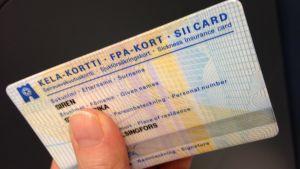Ett FPA-kort med namn och andra uppgifter. En hand håller i kortet.