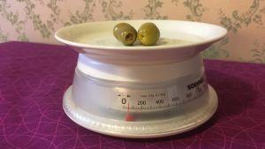 två oliver på ett vitt fat står på hushållsvåg på lila duk och med gammaldags grön tapet i bakgrunden