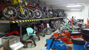 """Många äldre, men snyggt fixad mopeder parkerade på golv och en """"hylla"""" i en verstad."""