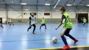 En pojke har bollen under kontroll medan en annan försöker täcka.