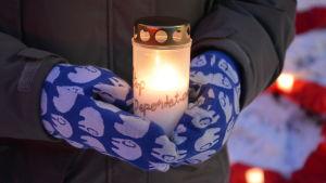En person håller i ett levande ljus under en demonstration.