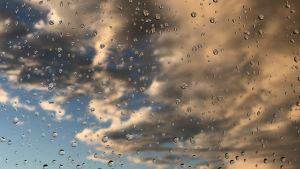 rengdroppar på fönsterruta, solbelysta moln utanför.