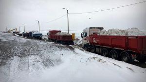 Lastbilar transporterar snö på Ärtholmen i Helsingfors.
