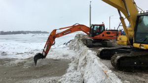 Grävmaskiner blandar snö som dumpats i havet på Ärtholmen i Helsingfors.