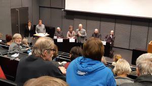publik i Åbo Akademis auditorium. Publiken fotad bakifrån och panel med 7 personer längst fram.