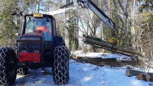 En man i en traktor tar upp stockar med en grip.