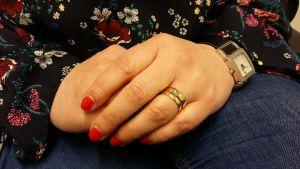 Kvinnohänder i famnen, rödlackade naglar och vigselring.