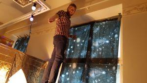 yngre rödskäggig man med bruna byxor och brunvit skjorta står på hög stege mot fönster beklätt med blått lakan med stjärnor