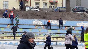 skolgård med springande elever vid stora ljusblåa trätrappor. Det är vinter och kallt. Eleverna har mössor