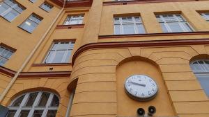 gul vägg med klocka på gammalt skolhus, med höga vita fönster