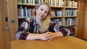 medelålders kvinna med långt blont hår står leende och knyter sina händer framför sig på ljusbrun hylla i bibliotek