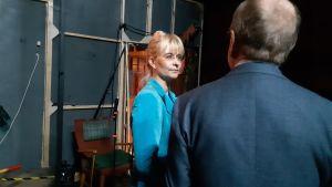 blond kvinna med glasögon och uppsatt år och ljusblå jacka står och talar med man i kostym som man bara ser bakifrån. Rummet är mörkt