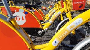 en lång rad gula cyklar i samma cykelställ på ett stentorg i Åbo