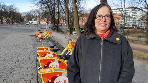 medelålders mörkhårig kvinna i grå kappa står framför en rad gula stadscyklar på stentorg i Åbo