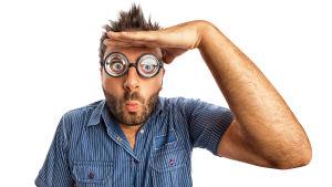 En man med lustiga glasögon som gör hans ögon stora tittar in i kameran och håller sin hand för pannan och har format sina läppar till en strut.