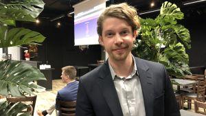 En man, Heikki Vestman,  står i ett öppet utrymme och tittar glatt in i kameran.