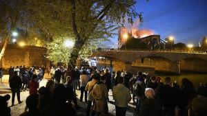 Parisare samlas vid floden Seine för att se på eldsvådan.