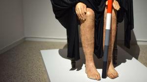 skulptur med händer och ben under svart skynke
