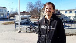 En man i 30-årsåldern står på en gård. Han har medellångt mörkt hår och en tjock mustasch.