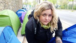 En blond kvinna vid ett tält på en gata.