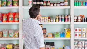 En fundersam man står och betraktar en butikshylla.