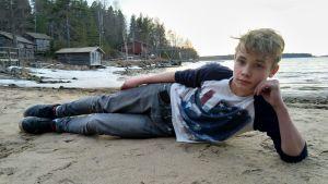 Oliver ligger på en strand och ser in i kameran.