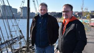 Tomas Gustafsson och mikael Martikainen på kajen i Sumparen i Helsingfors med segelfartyg i bakgrunden.