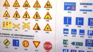 en plansch med många trafikmärken. Finns på en vägg i en trafikskola.