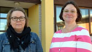 Två kvinnor framför en byggnad.