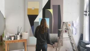 Tony Rubin står i sin ateljé och tittar på en stor tavla på väggen