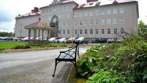 Bänk och lusthus framför en stor gammal sjukhusbyggnad. Gräsplan invid.