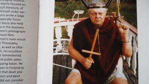 allvarlig äldre man med ockulta symboler i händer och på huvud