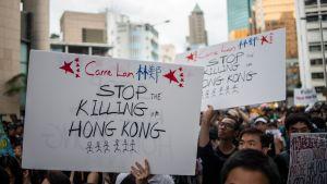 Demonstranter håller upp skyltar där de uppmanar Hongkongs ledare att sluta döda Honkong.