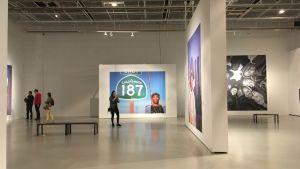 Bild från utställningen Uncategorized. På bilden syns några besökare som tittar på fotografier på kända rappare.