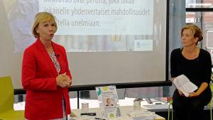 Anna-Maja Henriksson talar framför skärm.