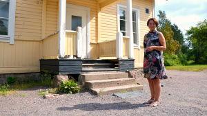 Kvinna poserar framför ett gult trähus.