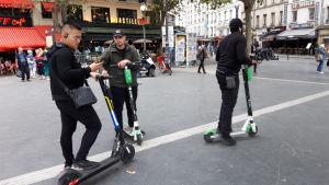 Tre Paris-killar med elscootrar