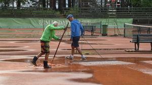 Två män torkar upp en regnvåt tennisbana.