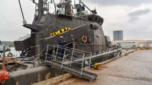 Krigsfartyg vid kaj i regn.