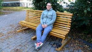 En man sitter på en gul parkbänk.