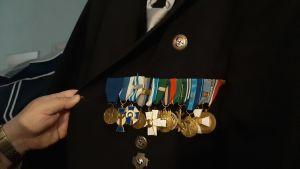en hand håller i en mörk kostym med medaljer på bröstet.