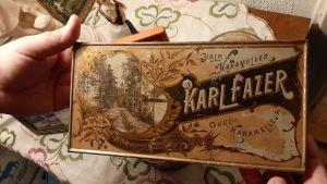två händer håller i en mycket gammal ask med halmkarameller från Karl Fazer. färgerna skriftar mellan ljust och mörkbrunt